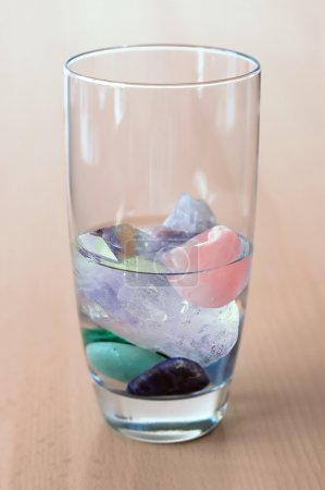 Crystals in glass of water on wooden table
