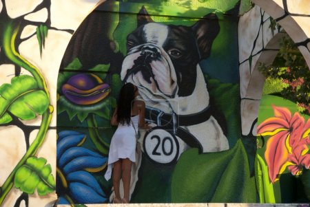 Woman kissing dog from 3D wall paintings...
