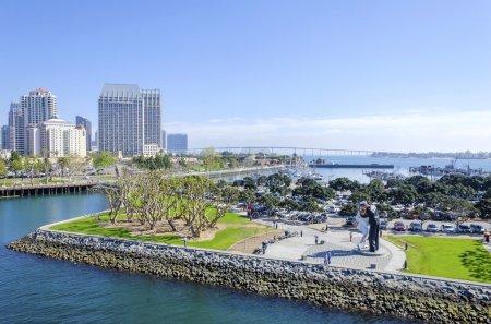 Photo pour Une vue de la statue de la capitulation sans condition dans la marina du centre de san diego en Californie du Sud dans les États-Unis d'Amérique. certains de l'architecture locale, les bâtiments commerciaux et le pont de coronado dans la ville. - image libre de droit