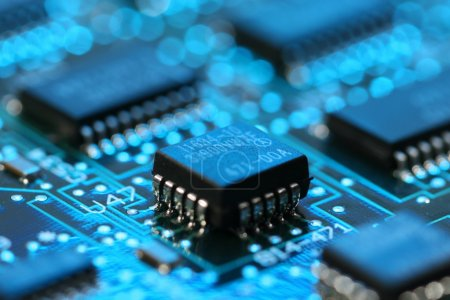 Photo for Infromation technology computer circuit board with transistor and blue light - Royalty Free Image