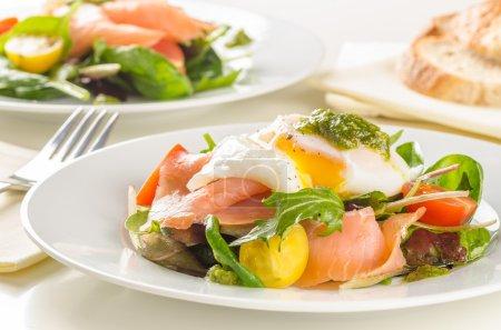 Poached egg salad with smoked salmon, cherry tomatoes and pesto.