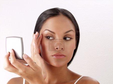 Latin woman applying makeup powder on white background,latin woman makeup.