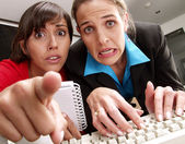 Two worried women watching a computer .
