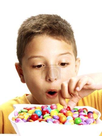 Foto de Niño está comiendo dulces sobre fondo blanco. - Imagen libre de derechos