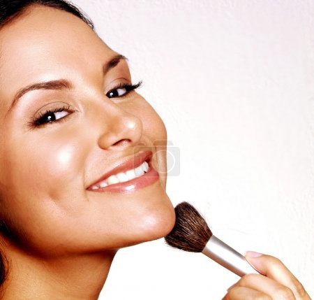 Latin woman applying blush on white background.