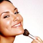 Latin woman applying blush on white background....