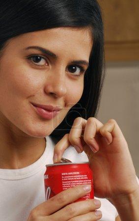 Cute brunette drinking out of a can