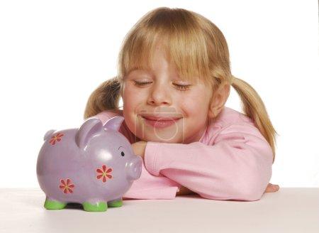 Little girl saving money using a piggy bank.