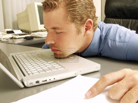 Exhausted young businessman sleeping at his desk