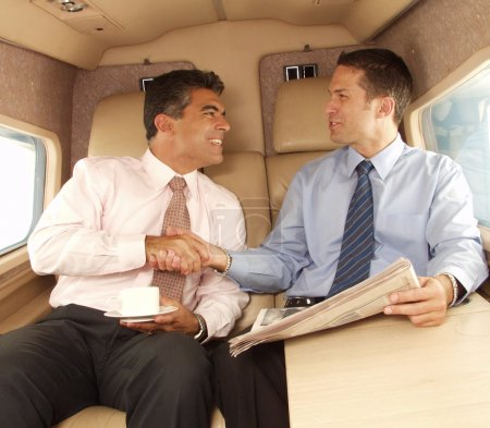 Business man shaking hands and working at private jet