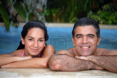 Latin couple enjoying together in a swimming pool.
