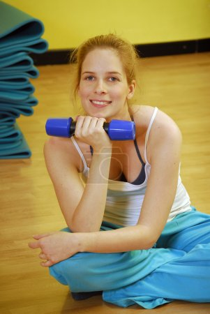Young blonde woman holding dumbbells in a gym