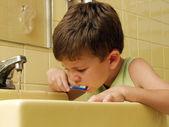 Kid brushing teeth in a bathroom.