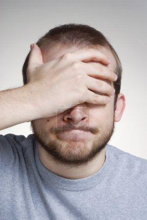 Photo pour Jeune homme expressif couvrant ses yeux . - image libre de droit