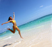 Happy latin young woman runing on the beach.