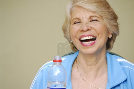 Happy senior woman drinking mineral water bottle