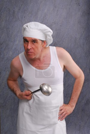 Cook holding a metallic spoon.