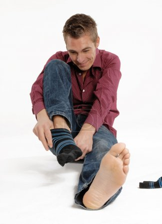 young man putting on sock