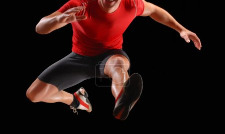 Photo for Athletic fitness man jump on black background. - Royalty Free Image