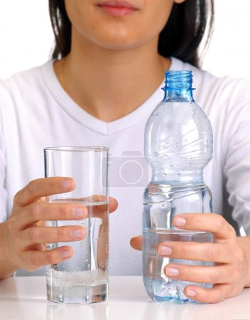 Young woman with buttle of water and glass.