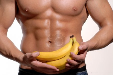 Photo for Shaped and healthy body man holding a fresh bananas - Royalty Free Image