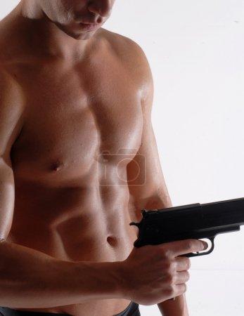 Muscular man holding gun