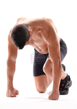 Photo for Healthy and fitness man on running start position on white background. - Royalty Free Image