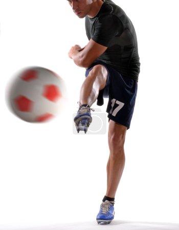 Soccer player kicking soccer ball.