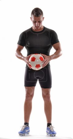 Soccer player holding a soccer ball.