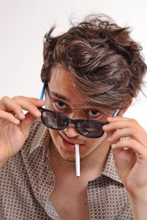 Smoking man wearing sunglasses.
