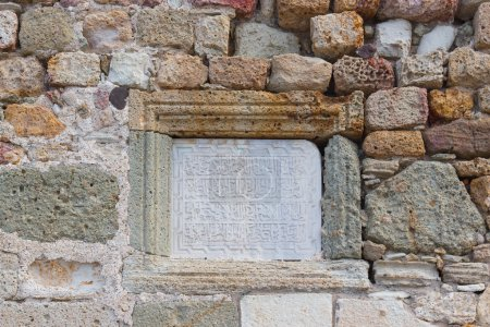 Photo for Wall of natural rough masonry. The city walls of Foca and Fife doors castle with Arabic inscription on marble table - Royalty Free Image