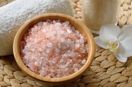 Photo pour Sel rose de l'himalaya. gros plan de sel rose spa dans un bol en bois avec fleur d'orchidée et serviette. - image libre de droit