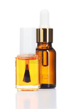 Photo pour Deux huiles naturelles pour les soins de beauté isolé sur fond blanc. ongles et cuticules huile et huile pour le corps dans une bouteille en verre. - image libre de droit