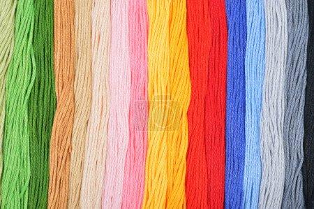 Photo pour Fils à broder colorés dans une rangée. Fond coloré . - image libre de droit