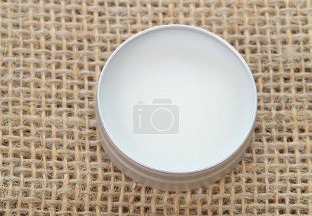 Photo pour Beurre de karité pur en étain métallique sur toile de lin. Baume à lèvres et baume beauté parfaits . - image libre de droit