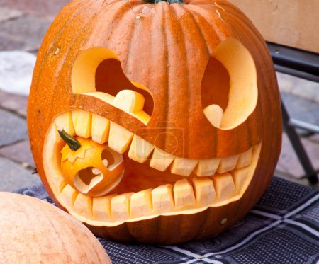 Photo for Cuted Halloween pumpkin eatind small pumpkin. - Royalty Free Image