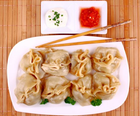 Dumplings on white plate with chopsticks and chilli sauce, view from top