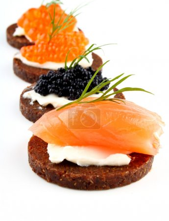 Black bread topped with salmon fish, trout and stu...