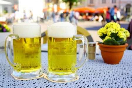 Photo for Two steins beer garden in the city, soft focus - Royalty Free Image