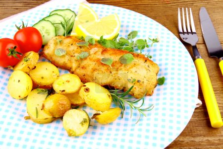 Rosemary potatoes with fried fish fillet and vegetables