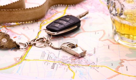 Car key with accident and beer mug on map