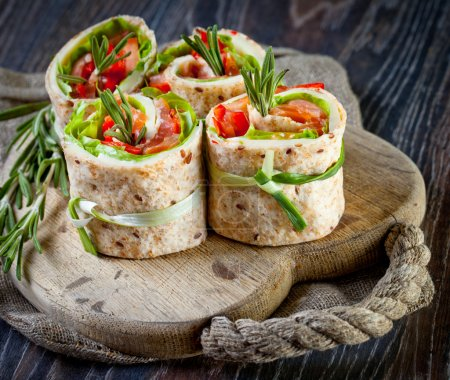 Photo for Salmon lavash rolls with fresh salad leafs - Royalty Free Image