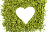 Powdered green tea forming heart shape isolated on white background