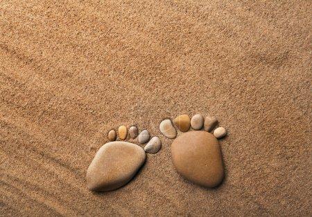 Photo pour Deux pieds traces faits d'une pierre de galets sur le désert de sable de mer, toile de fond texture - image libre de droit