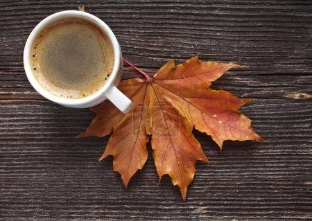 Photo pour Tasse à café sur les feuilles d'automne d'automne et fond de surface en bois - image libre de droit