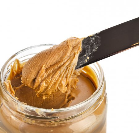 Glass with peanut butter creamy and knife
