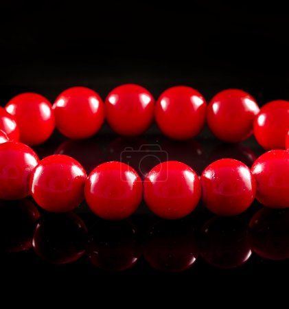 Beads of red coral with reflection