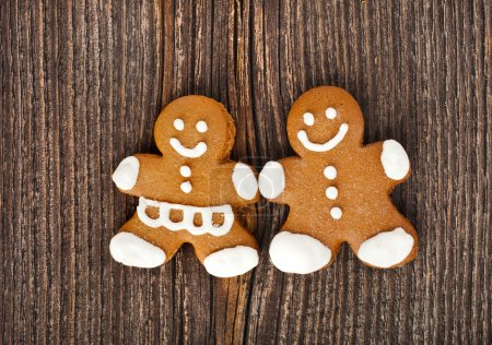 Photo for Fun Gingerbread couple on vintage wooden surface top view background - Royalty Free Image