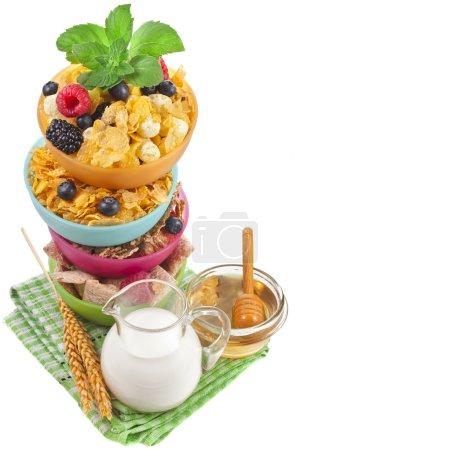 Border of corn flakes with fresh berries, milk, honey