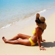 Young woman in a yellow swimsuit, a hat and sungla...